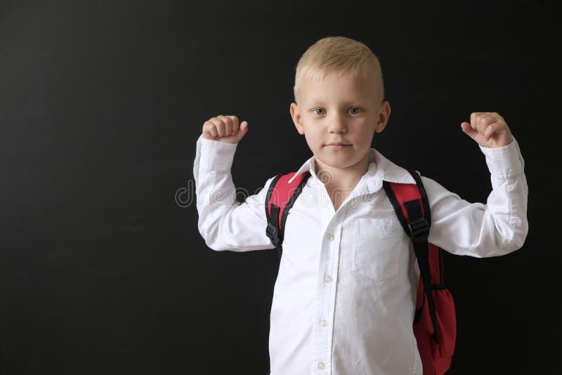 De nuevo a escuela Niño pequeño lindo en la pizarra Niño de la escuela primaria con el bolso Concepto de la educaci?n foto de archivo libre de regalías