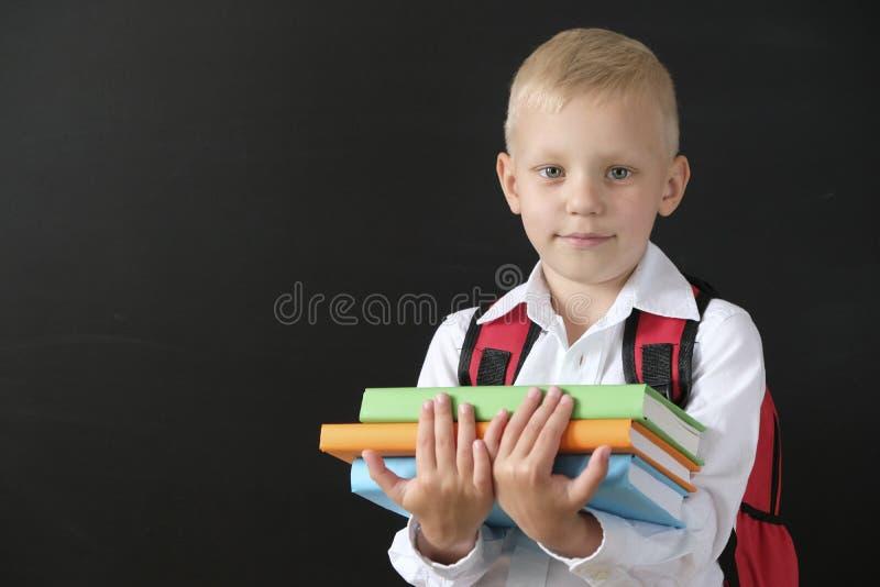 De nuevo a escuela Niño pequeño lindo en la pizarra Niño de la escuela primaria con los libros y el bolso Concepto de la educaci? imágenes de archivo libres de regalías