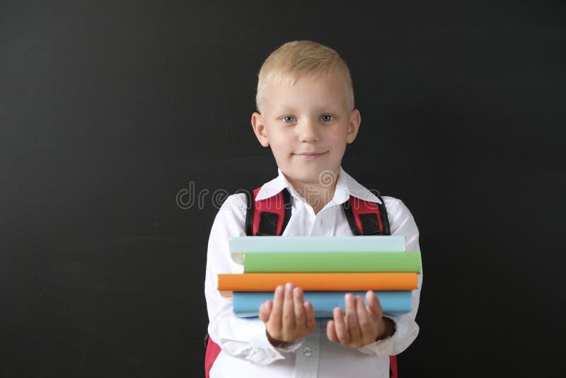 De nuevo a escuela Niño pequeño lindo en la pizarra Niño de la escuela primaria con los libros y el bolso Concepto de la educaci? fotos de archivo