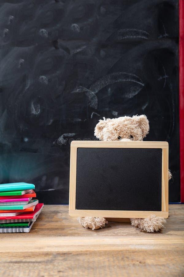 De nuevo a escuela Oso de peluche y pizarra en blanco con el marco en el escritorio de madera imagen de archivo