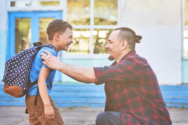 De nuevo a escuela Padre e hijo felices delante de la escuela primaria El padre lleva al niño a la escuela primaria foto de archivo