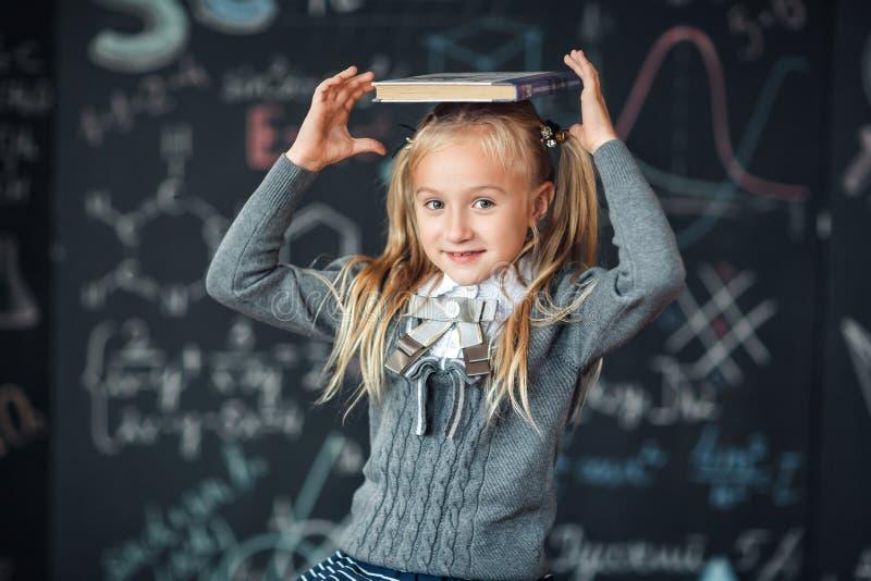 De nuevo a escuela poca muchacha rubia en niño del uniforme escolar de la escuela primaria guarda los libros en su cabeza Educaci foto de archivo