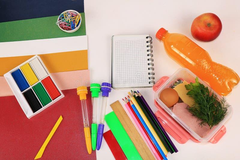 De nuevo a escuela, surtido de lápices coloreados, plumas y reglas, jugo y desayuno de la escuela en un extracto muy brillante de foto de archivo libre de regalías