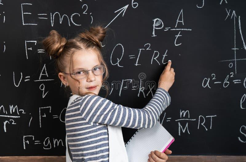 De nuevo a escuela: una colegiala elegante de la muchacha escribe fórmulas complejas en tiza en una pizarra Retrato fotos de archivo libres de regalías
