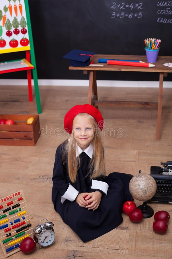 ?De nuevo a escuela! Una muchacha en el uniforme escolar que se sienta en una lecci?n La colegiala responde a la lecci?n En la pi foto de archivo libre de regalías