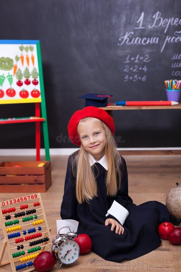 ?De nuevo a escuela! Una muchacha en el uniforme escolar que se sienta en una lecci?n Responde a la lecci?n En la pizarra en la l imagen de archivo