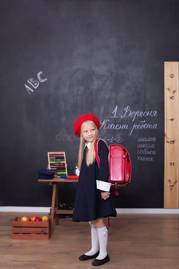 ?De nuevo a escuela! Una muchacha se coloca en escuela con una mochila roja Responde a la lecci?n Concepto de la escuela En la pi fotos de archivo