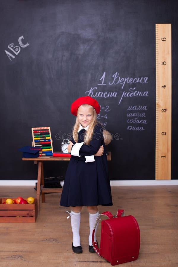 ?De nuevo a escuela! Una muchacha se coloca en escuela con una mochila roja Responde a la lecci?n Concepto de la escuela En la pi foto de archivo libre de regalías