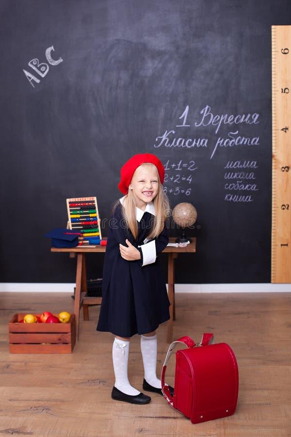 ?De nuevo a escuela! Una muchacha se coloca en escuela con una mochila roja Responde a la lecci?n Concepto de la escuela En la pi imagen de archivo