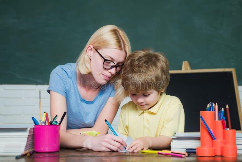 De nuevo a escuela y a tiempo feliz D?a de los profesores Profesor que ayuda al muchacho joven con la lecci?n Niño y profesor cer fotos de archivo libres de regalías