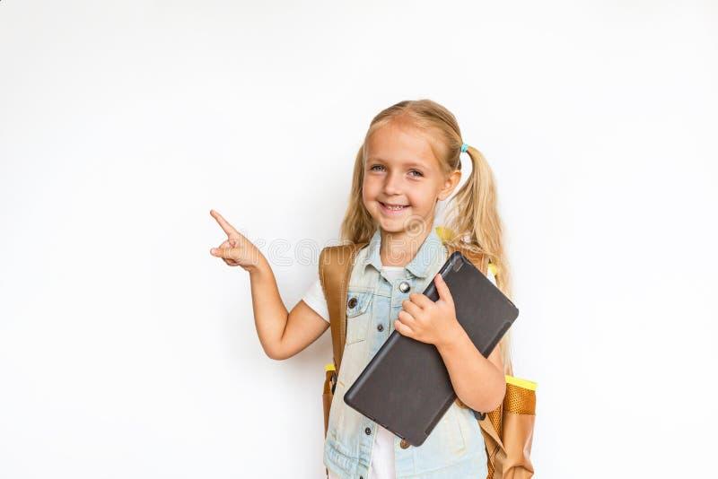 De nuevo a escuela y a tiempo feliz Niño lindo con el pelo rubio en el fondo blanco Cabrito con el morral Muchacha lista para est foto de archivo
