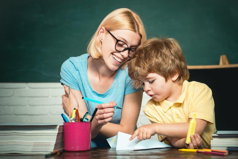 De nuevo a escuela y a tiempo feliz Ni?os felices de la escuela Educaci?n y aprendizaje de concepto de la gente Profesor y ni?o foto de archivo libre de regalías