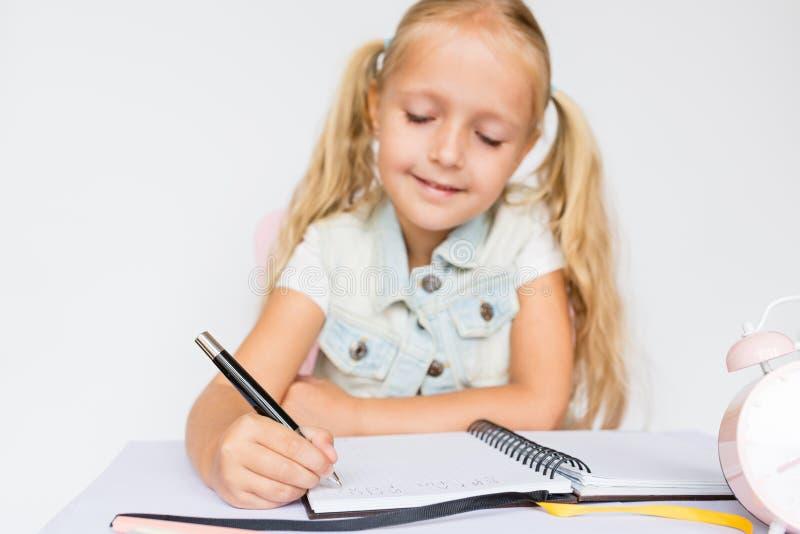 De nuevo a escuela y a tiempo feliz Pluma de tenencia de los niños y escritura en cuaderno en el fondo blanco Ni?o que hace la pr fotografía de archivo