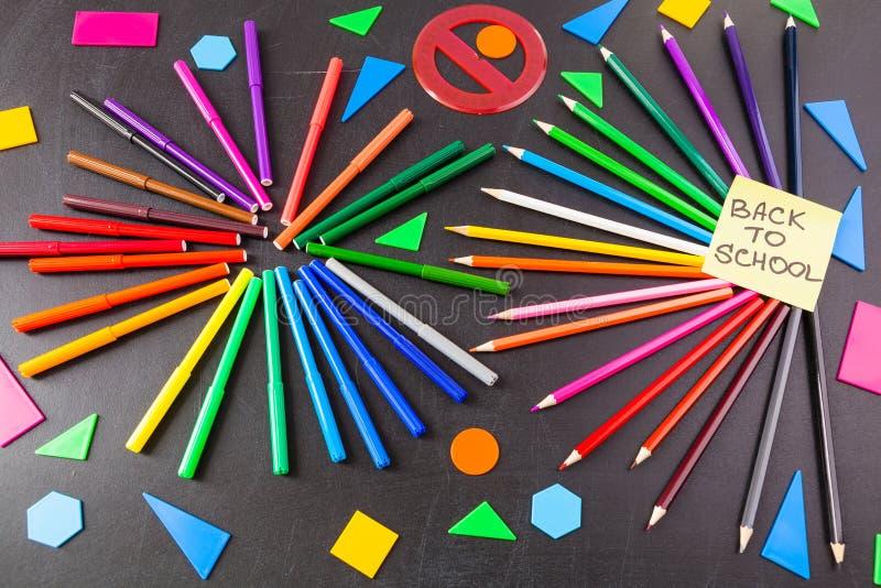 De nuevo a fondo de la escuela con muchos rotuladores coloridos y lápices coloridos y a título de nuevo a la escuela escrita fotos de archivo