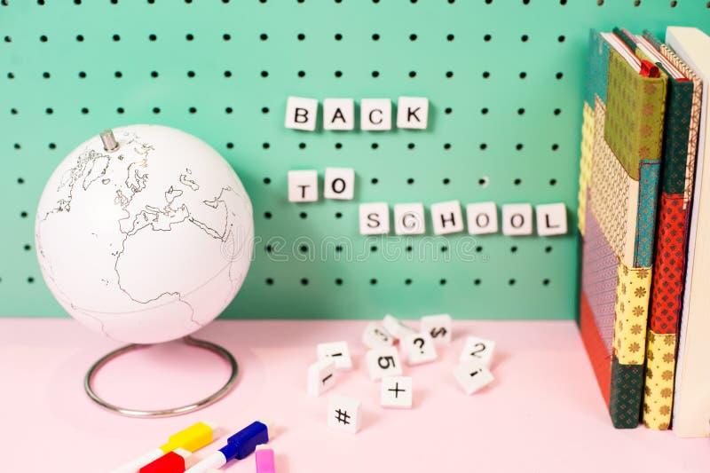De nuevo a fuentes de escuela Globo blanco y letras de madera en un tablero, colores en colores pastel foto de archivo libre de regalías