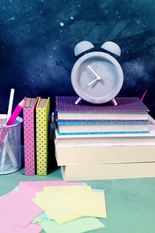 De nuevo a la composici?n de la escuela con el despertador y los libros del vintage fotografía de archivo libre de regalías