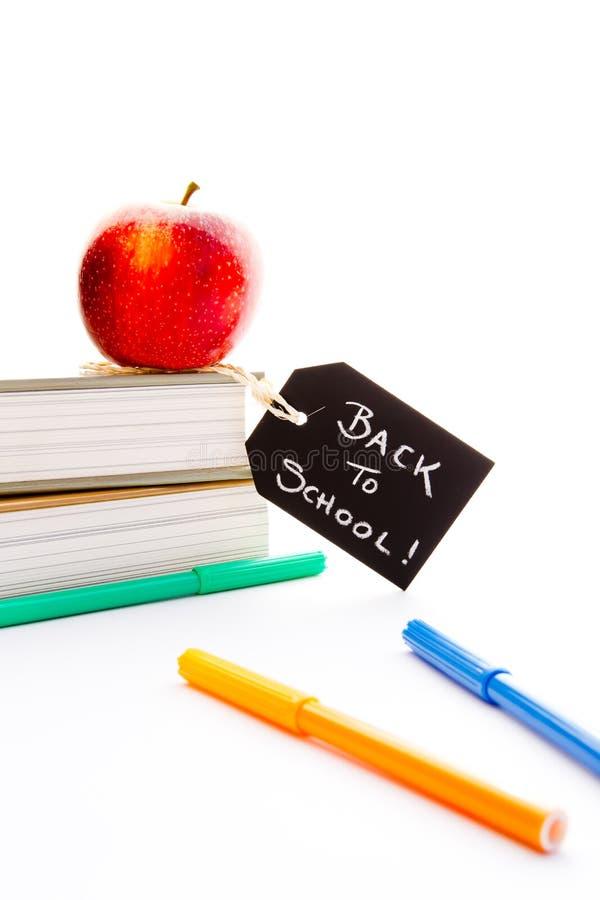 De nuevo a la escuela - Apple, libros y plumas rojos foto de archivo