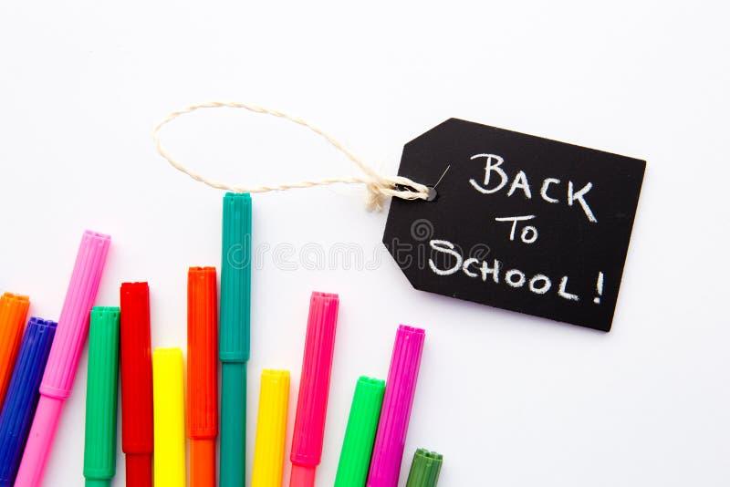De nuevo a la escuela - plumas coloreadas en el fondo blanco foto de archivo