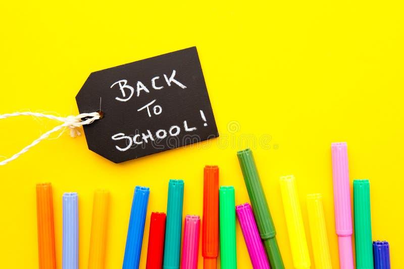 De nuevo a la escuela - plumas coloreadas en fondo amarillo foto de archivo libre de regalías