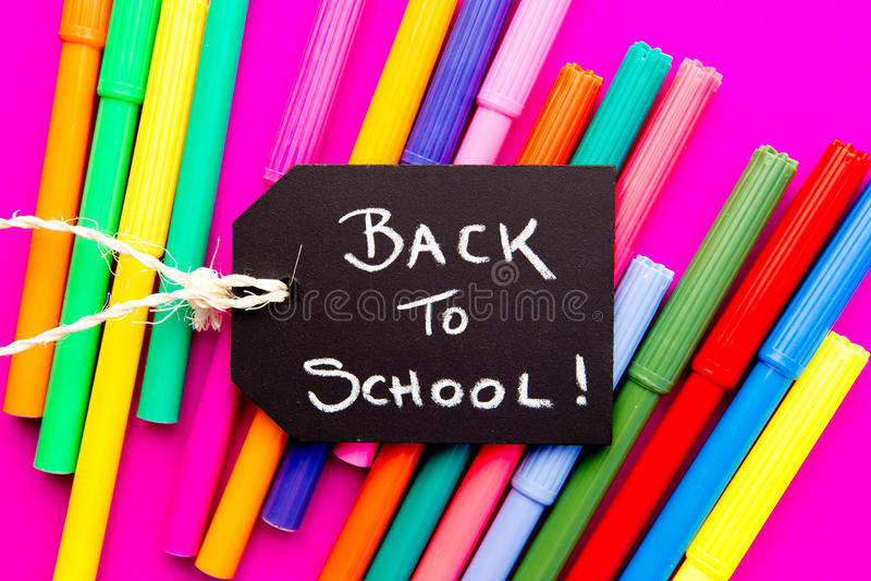 De nuevo a la escuela - plumas coloreadas en fondo rosado imágenes de archivo libres de regalías