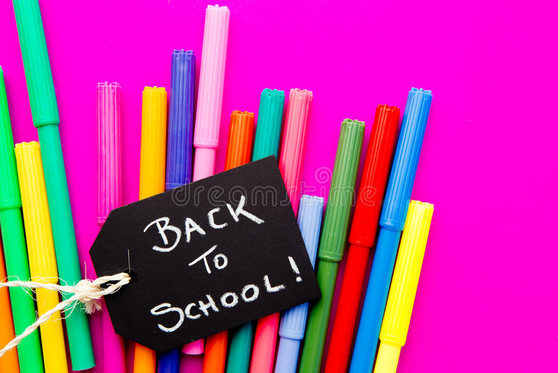 De nuevo a la escuela - plumas coloreadas en fondo rosado foto de archivo libre de regalías