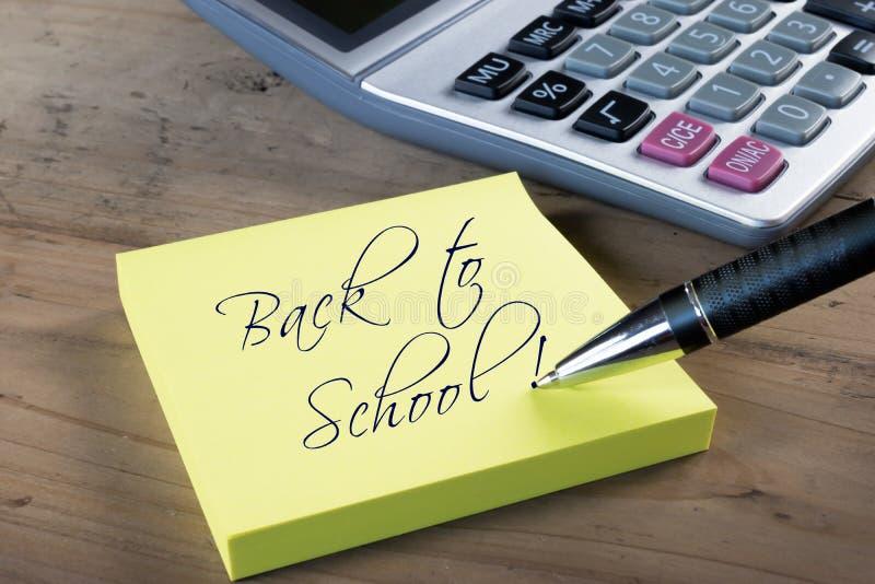 De nuevo a la nota de la escuela escrita con la pluma Calculadora en fondo imagen de archivo libre de regalías