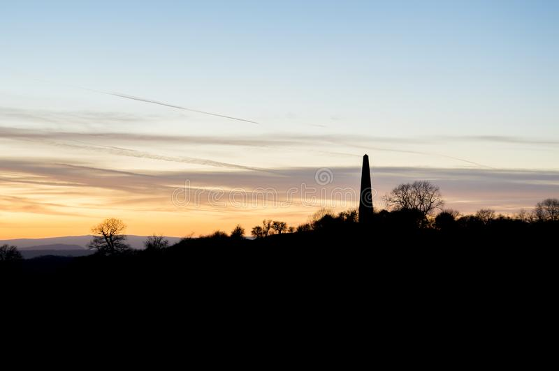 De Obelisk in Eastnor, Herefordshire tegen de zonsondergang op een de wintersmiddag die wordt gesilhouetteerd het UK stock foto's