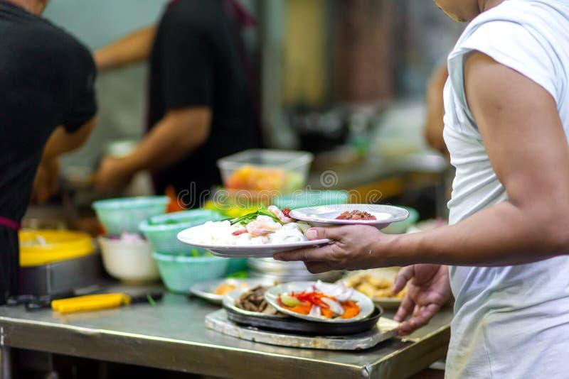 De ober pakt de pijlen op met de voltooide maaltijd van de distributie stock afbeeldingen