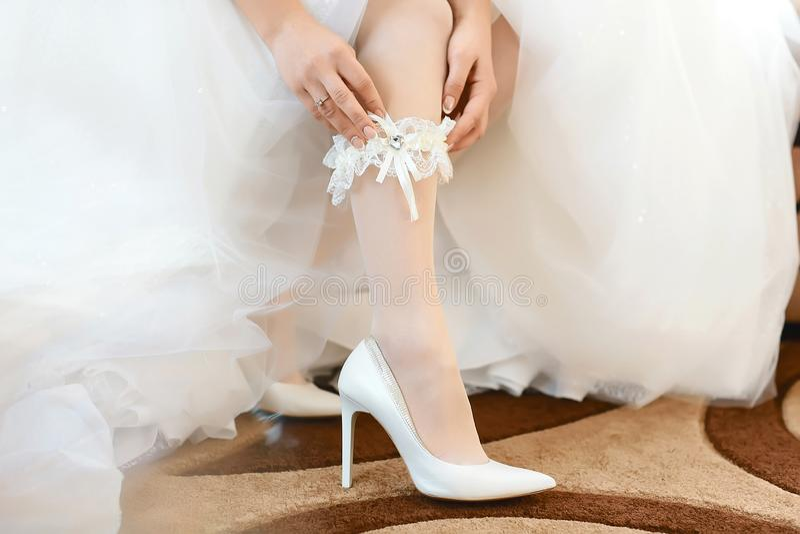 In de ochtend, dragen de bruid in kousen en een witte huwelijkskleding in witte hielschoenen een kouseband op haar been, is de br royalty-vrije stock afbeelding