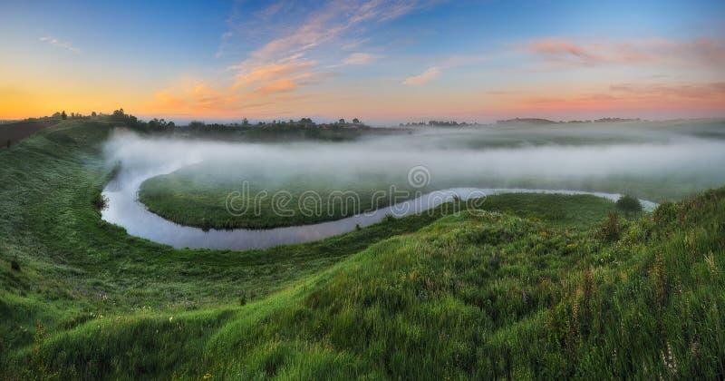 De ochtend? gebied van de lente van groen gras en blauwe bewolkte hemel Zonsopgang in de vallei van de schilderachtige rivier royalty-vrije stock foto