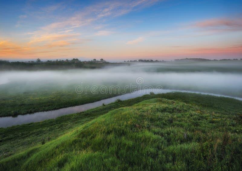 De ochtend? gebied van de lente van groen gras en blauwe bewolkte hemel Zonsopgang in de vallei van de schilderachtige rivier stock afbeelding
