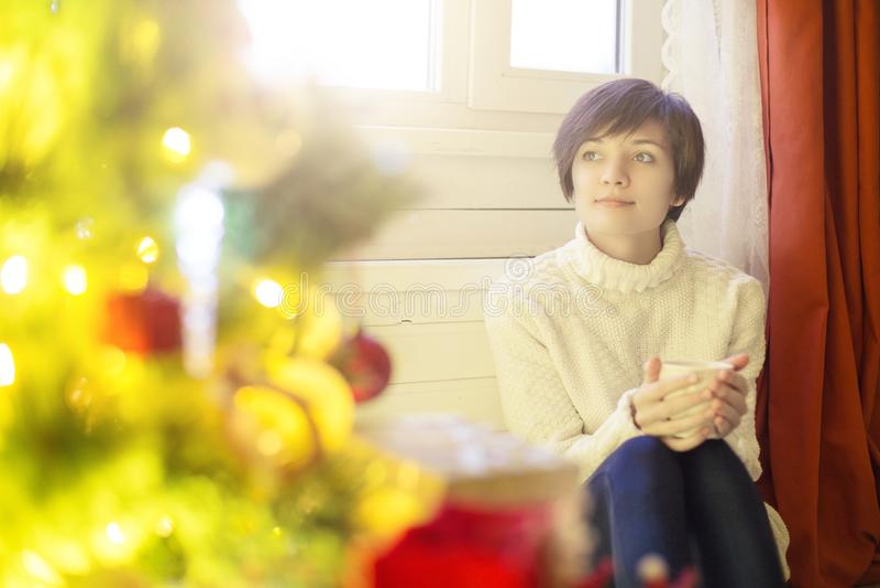 De ochtend van Kerstmis Jonge vrouwenzitting in de woonkamer, holding een kop thee in haar handen stock foto