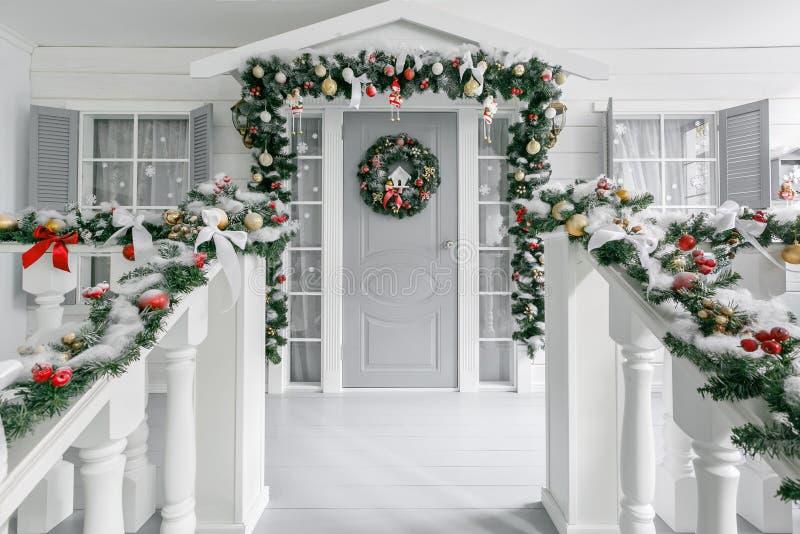 De ochtend van Kerstmis portiek een plattelandshuisje met een verfraaide deur met een Kerstmiskroon Het sprookje van de winter royalty-vrije stock afbeeldingen