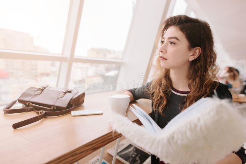 In de ochtend zit het meisje in een koffie Zij kijkt uit het venster, houdt een koffie en een notitieboekje in zijn handen stock foto