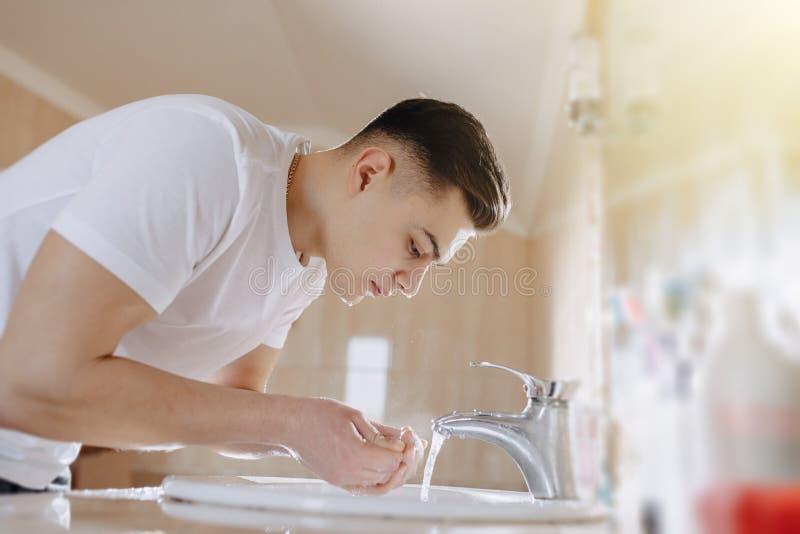 De ochtendhygi?ne, wordt de jongen gewassen in een wasbassin met nevel van water stock fotografie