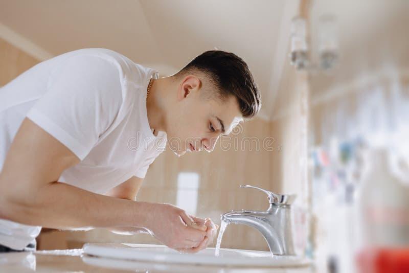 De ochtendhygi?ne, wordt de jongen gewassen in een wasbassin met nevel van water stock foto