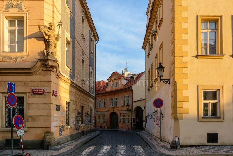 De ochtendzon verlicht een straat in Praag stock foto's