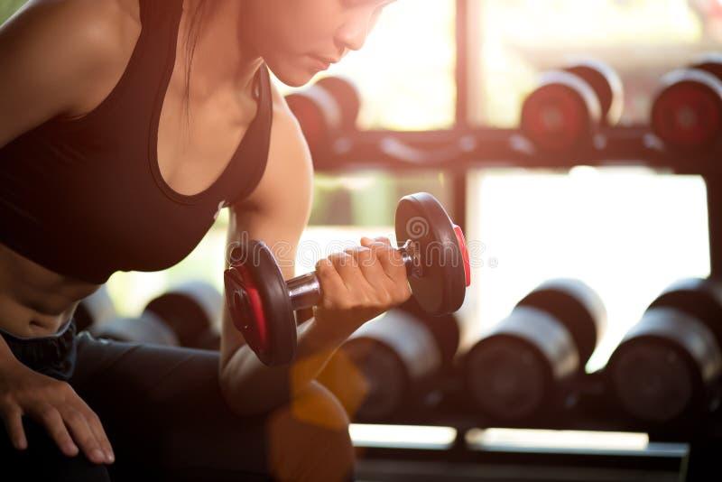 De oefening van de de holdingsdomoor van de vrouwenhand in gymnastiek Geschiktheids spierlichaam met reeks zwarte gewichten stock foto's