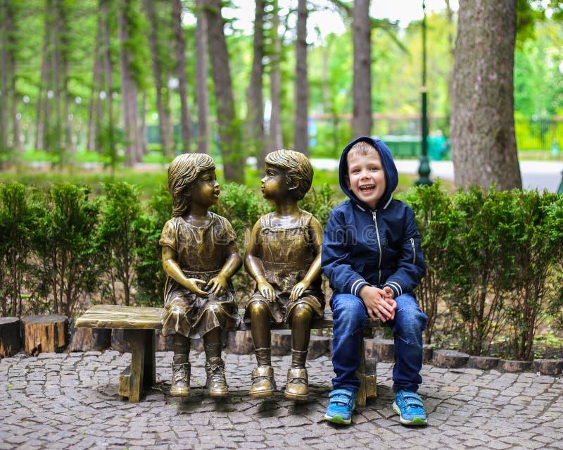 De Oekraïne, Kharkiv - mag, 2019: Het gelukkige glimlachende kind zit op een bank in het park royalty-vrije stock fotografie
