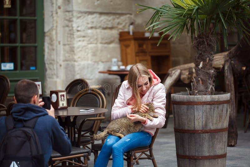 De Oekraïne, Lviv - Mei 13, 2019: De toeristen strelen een kattenzitting in een koffie stock fotografie
