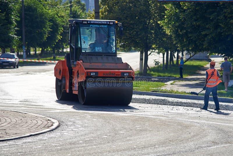 De Oekraïne, 14 shostka-Juni, 2019: Een groep arbeiders en bouwmachines voor asfaltwegen bij de bouwwerf royalty-vrije stock afbeeldingen
