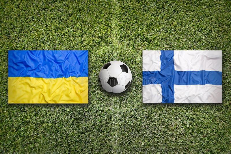 De Oekraïne versus Montenegro De vlaggen van Finland op voetbalgebied royalty-vrije stock afbeelding