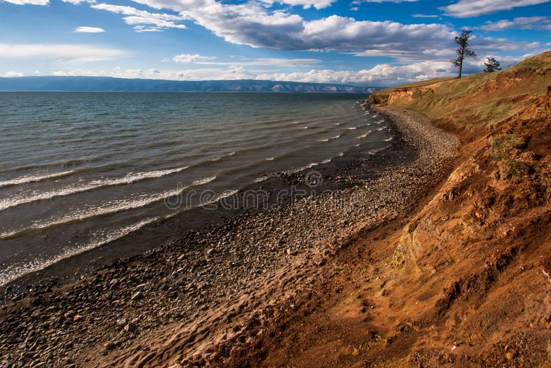 De oever van het meer van Baikal met bergen in de achtergrond en de mooie wolken en het licht royalty-vrije stock afbeeldingen