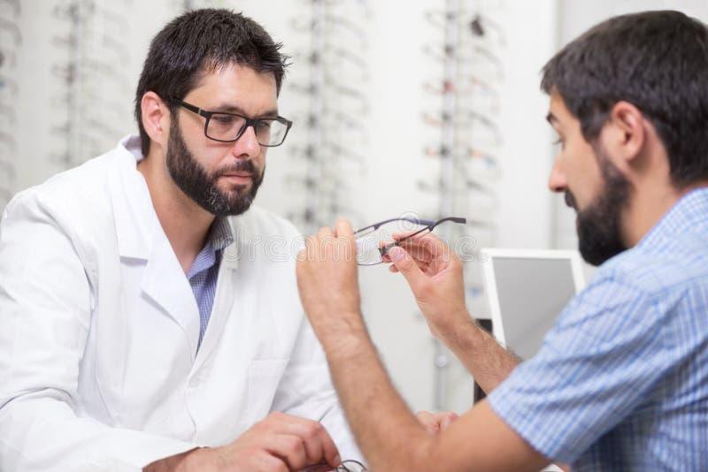 De oftalmoloog die oogglazen voor aanbieden probeert uit Optometrist die een paar glazen aanbieden te dragen royalty-vrije stock afbeelding