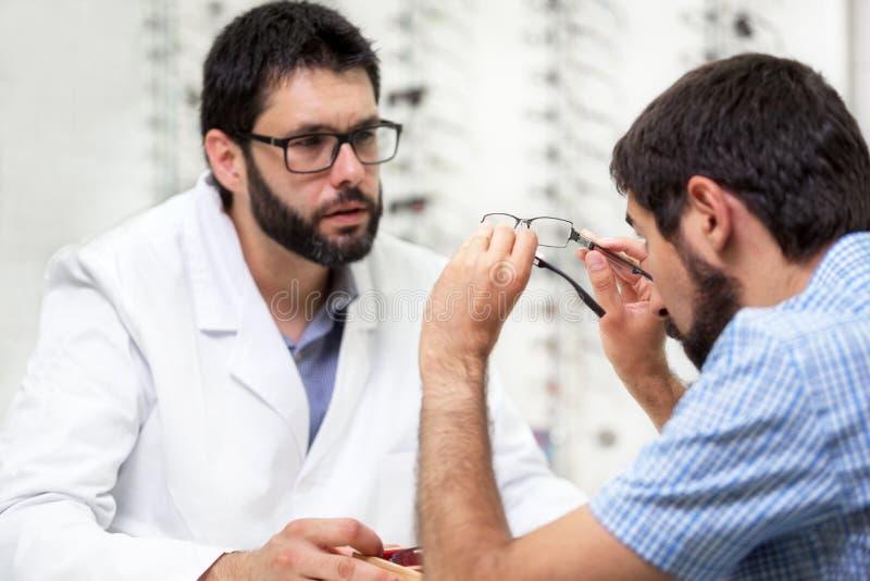 De oftalmoloog die oogglazen voor aanbieden probeert uit Optometrist die een paar glazen aanbieden te dragen stock afbeeldingen