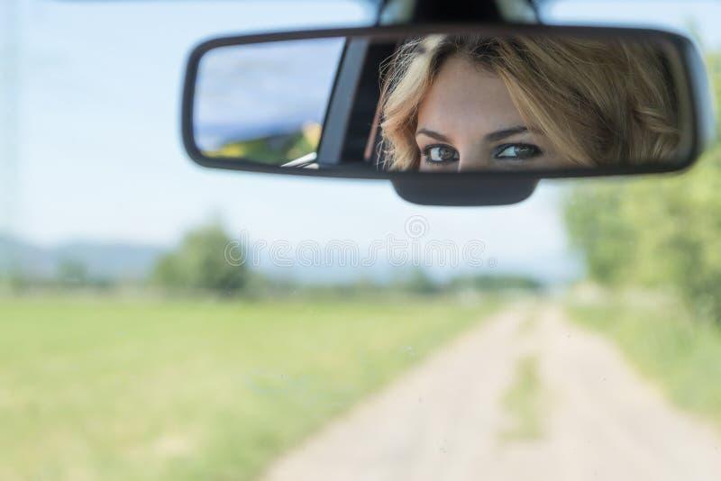 De ogen van de jonge bestuurdersvrouw worden weerspiegeld in rearview royalty-vrije stock afbeelding