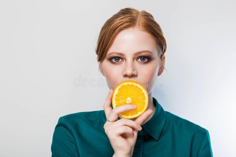 De ojos verdes hermoso, mujer del pelirrojo cubre sus labios con una rebanada de naranja Piel bien preparada, cara limpia con maq fotografía de archivo libre de regalías