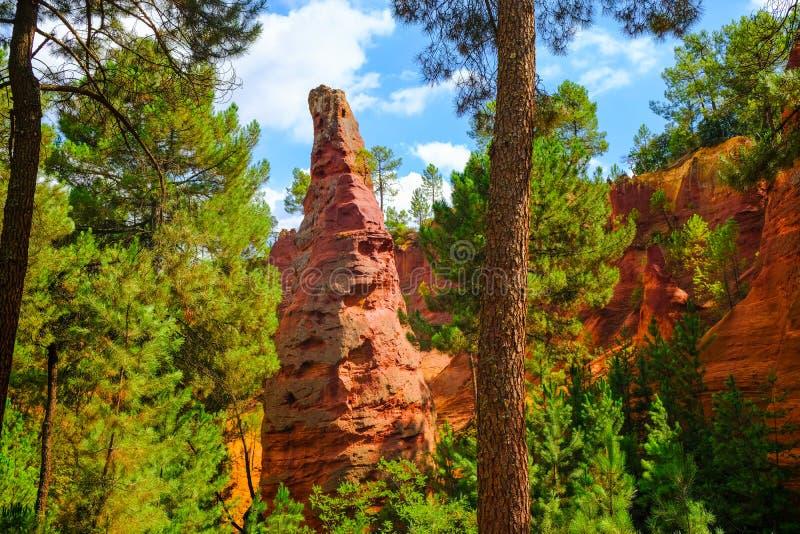 De okerstorting van Roussillon: Mooie grote rode oker piek, blauwe hemel met wolken en groene pijnbomen royalty-vrije stock afbeelding