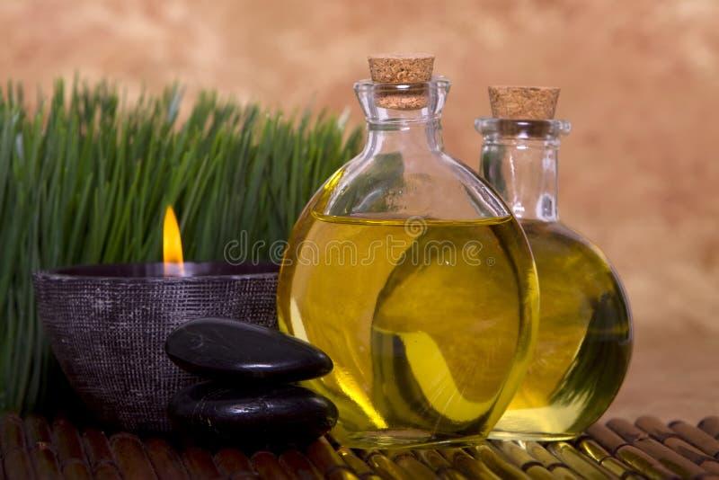De oliën en de kaars van de massage met groen gras stock afbeeldingen