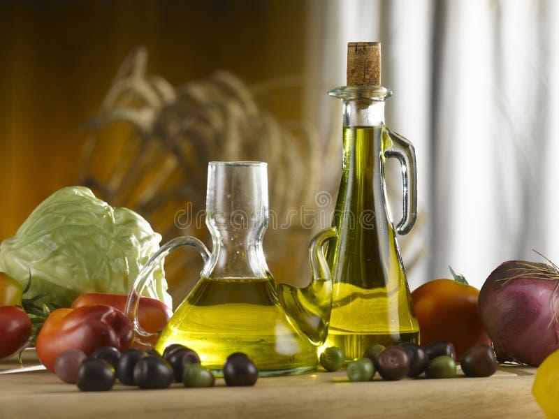 De olie- en azijnstelletjes en de groenten van het olijfolieglas stock foto